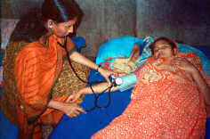 Copyright © 2002 Jean Sack/ICDDRB, Courtesy of Photoshare. Physician (L) at Matlab Hospital, Bangladesh, consulting a mother whose daughter is sick with diarrhea. The mother is feeding her daughter a rice-based Oral Rehydration Solution (ORS)